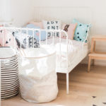 A modern, pastel shared baby and toddler room