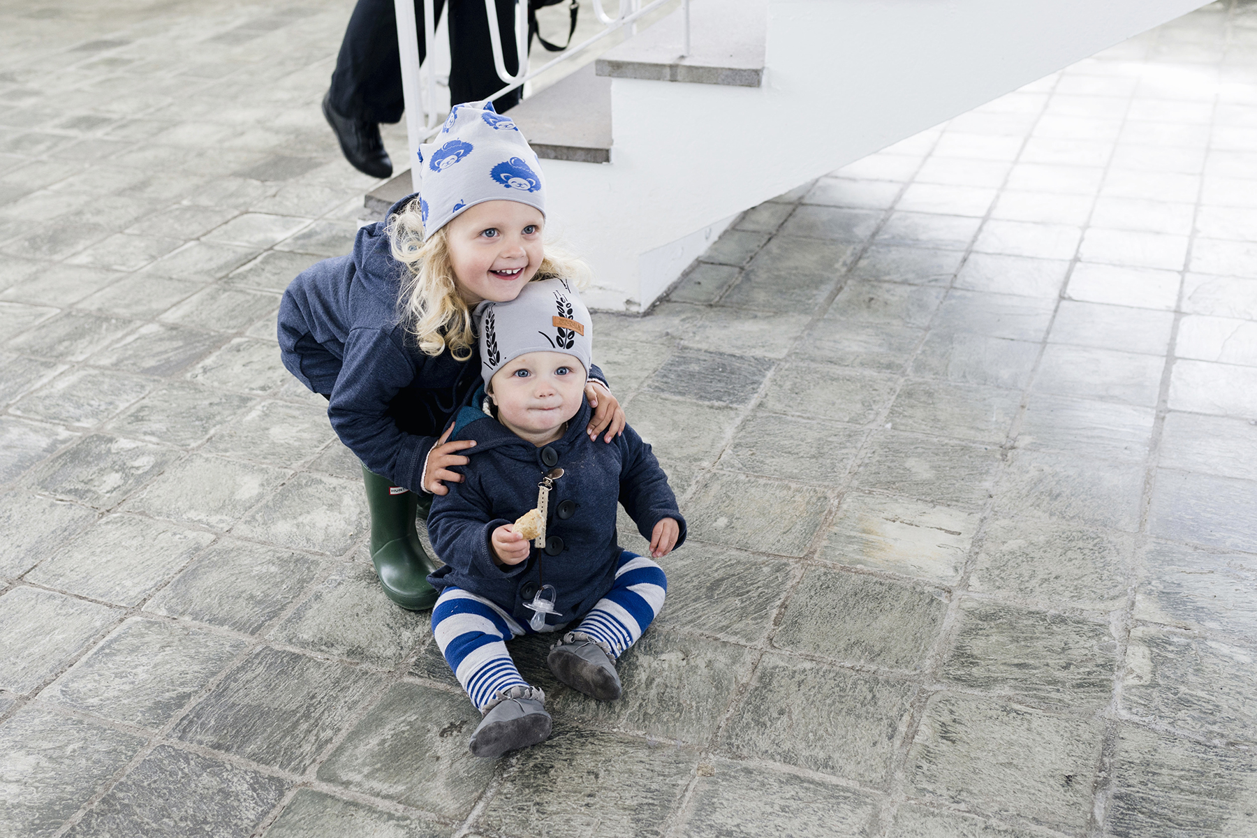 Sweet siblings at Reykjavik Hallgrimskirka, Iceland with young kids - family travel with a baby & toddler | Happy Grey Lucky