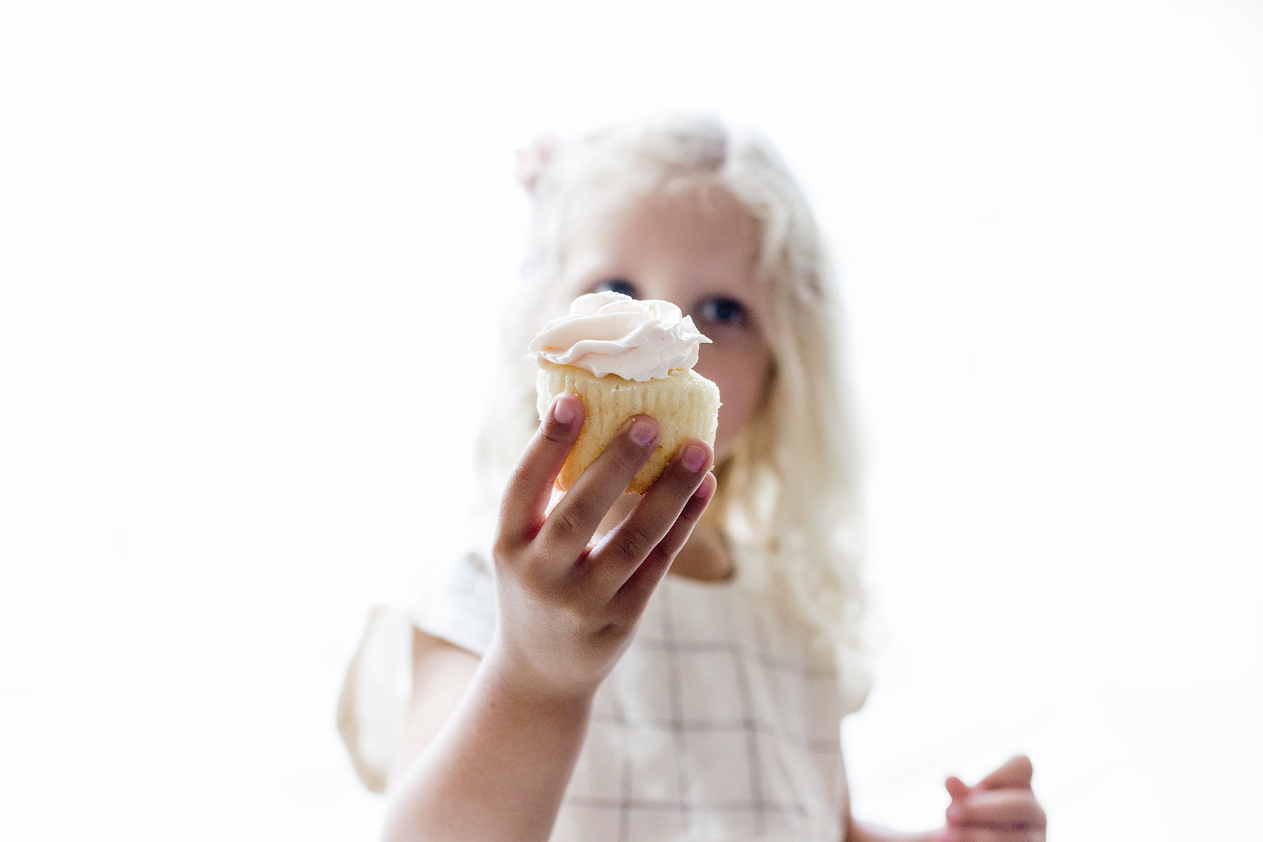 Girl holding cupcake | A wild + boho baby shower with pastel colours + rustic details
