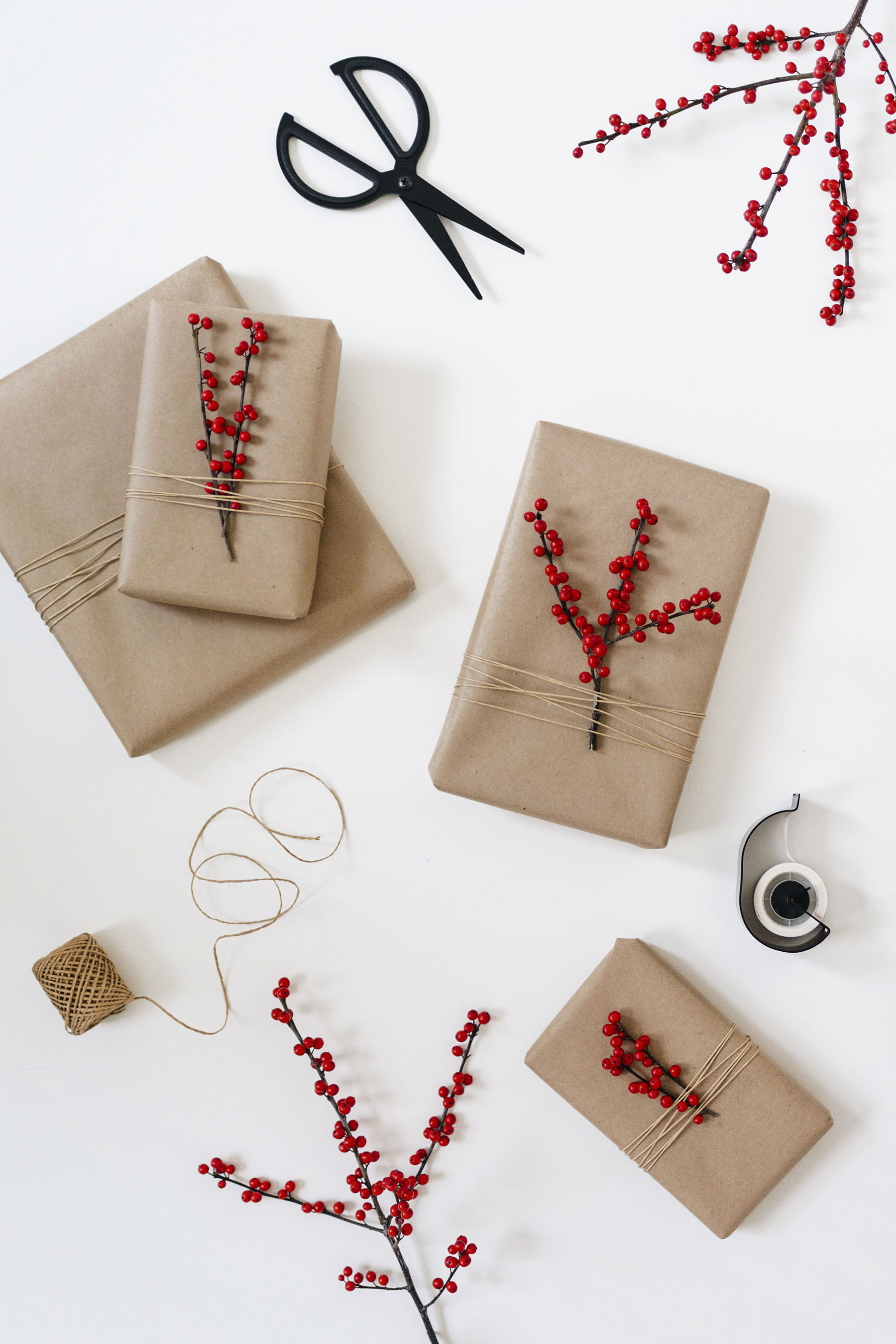 Christmas wrapping with brown postal paper and red Winterberry branches